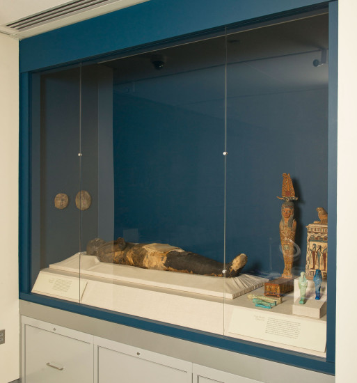 The Goucher mummy as currently displayed in the museum.  She is surrounded by funerary objects which would have typically been placed with the deceased.  Image courtesy of Goucher College.