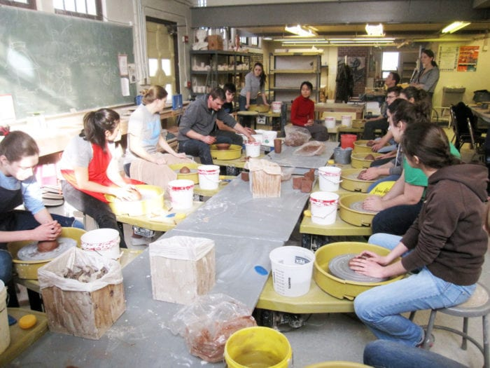 The class at their wheels, watching Matt Hyleck throw a bowl for a kylix.