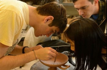Travis Schmauss draws a tondo with a compass as Ross Brendle and Haley Huang look on.