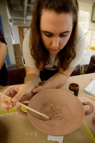 Elizabeth Winkelhoff uses a linierhaar brush to being painting the relief lines on her group's cup.