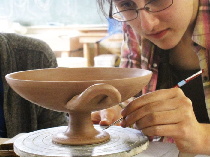 Anna Soifer puts the final touches on the painted inscription on the foot of a kylix.