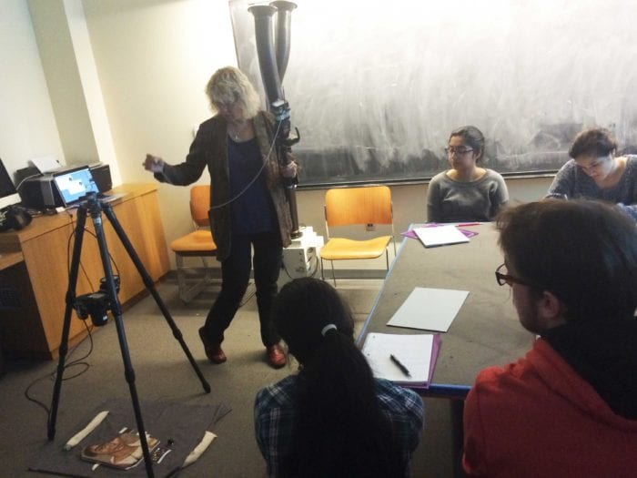"""Carla Schroer of CHI demonstrates the set up for RTI.  """"Portrait of a Young Man"""" is lying on a padded layer below (a very secure) camera on a (very secure) tripod.  She is holding the flash unit and stretching out the string that will be our measuring tool."""