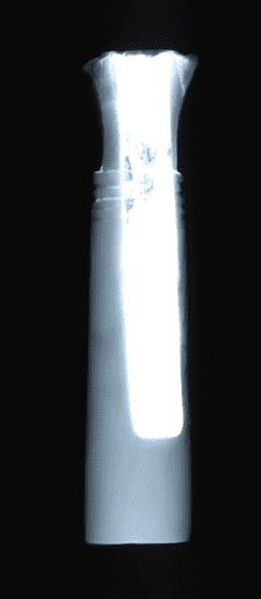 """An x-ray showing a dense tube like """"sleeve"""" in the interior of the object."""